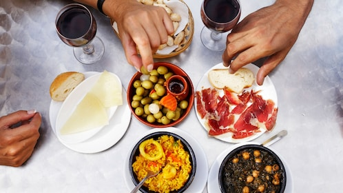 A table full of Spanish food with hands grabbing at it.