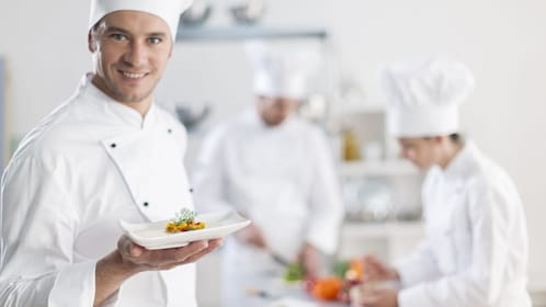 A chef in a kitchen holding up food.