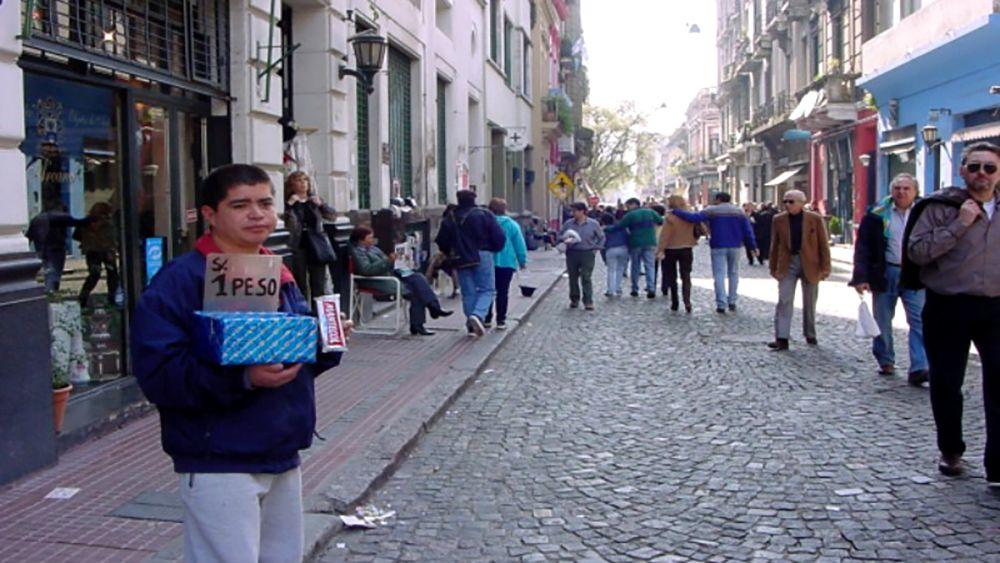 A young man selling goods for a peso in Buenos Aires