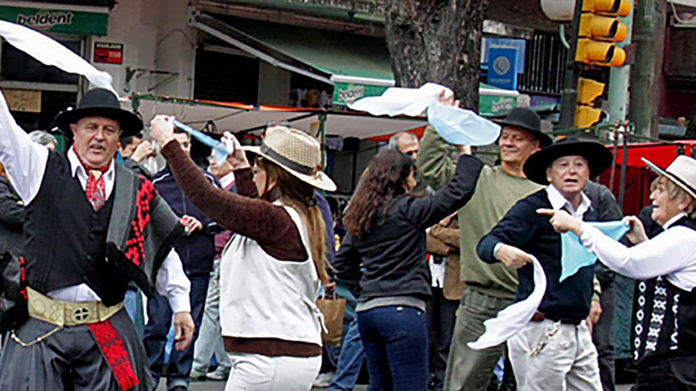 A group of men and women dancing in the street in traditional clothes and hats