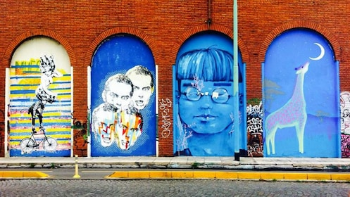 Four archways on the side of the building tagged with four distinct graffiti images