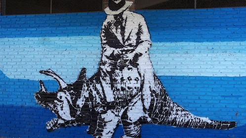 A tagged black and white stencil image of a man riding a Triceratops with a blue background