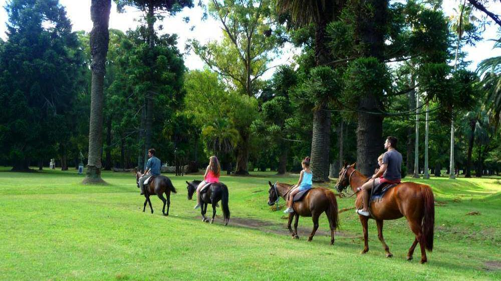 A group on horseback through the grounds of La Candelaria Ranch