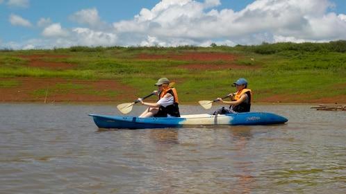 Two people enjoying a scenic kayak tour in Chiang Mai