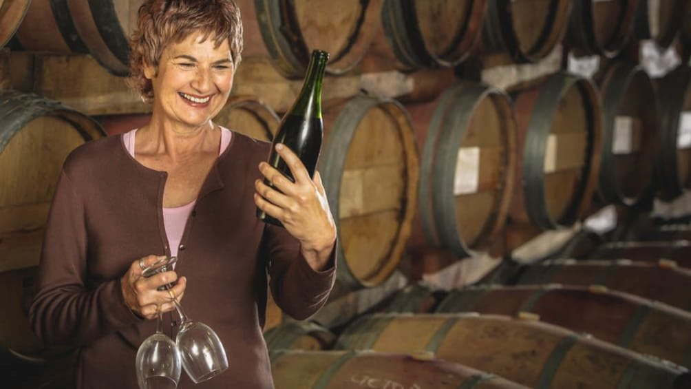 Show item 2 of 5. Smiling woman in wine cellar next to several barrels of wine.