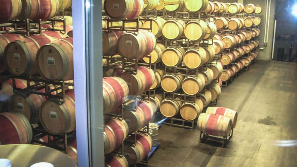 Show item 5 of 5. Wine cellar with several barrels of wine on racks.