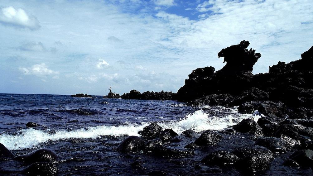 正在顯示第 5 張相片,共 5 張。 Man fishes in the distance of the rocky shore of Jeju Island