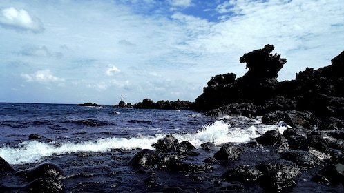 Man fishes in the distance of the rocky shore of Jeju Island