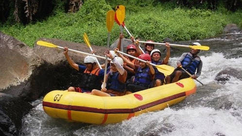 Tourist group in water raft moving down river.