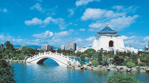 Serene view of Taipei on a blue sky day overlooking a white bridge and building