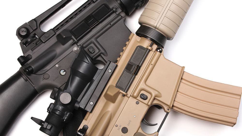 Close up of black and tan colored rifles.
