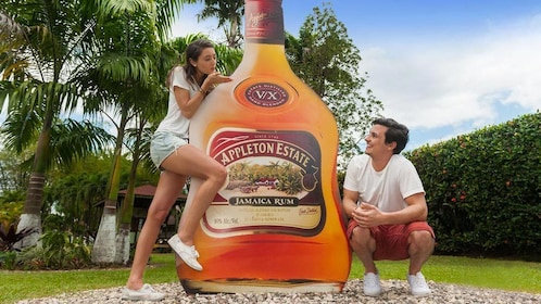 Couple posing with a cut out of a rum bottle at the Appleton Estate in Jamaica