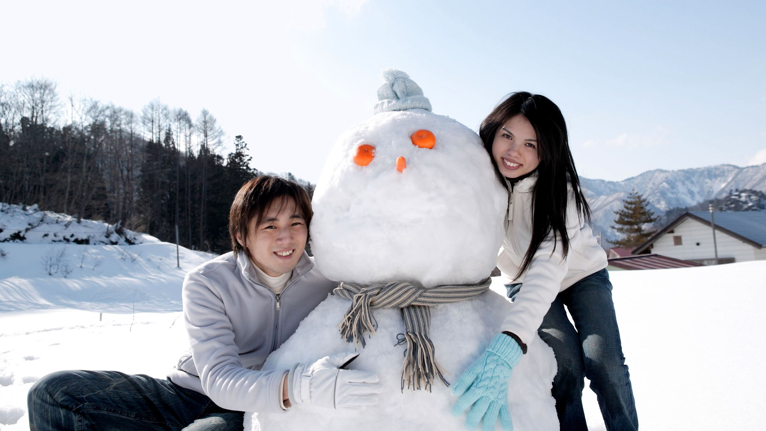 Young couple with snowman