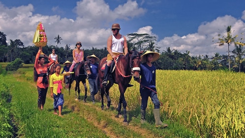 people riding in group in field in bali