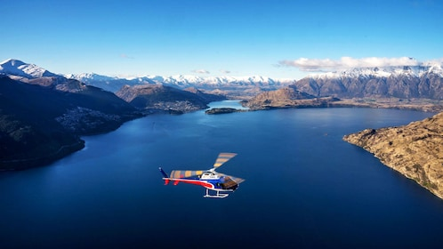 Helicopter flying over Lake Wakatipu in New Zealand