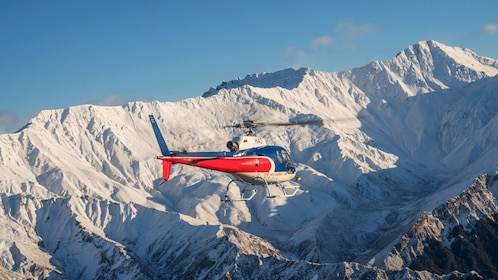 Helicopter flying past mountains in New Zealand