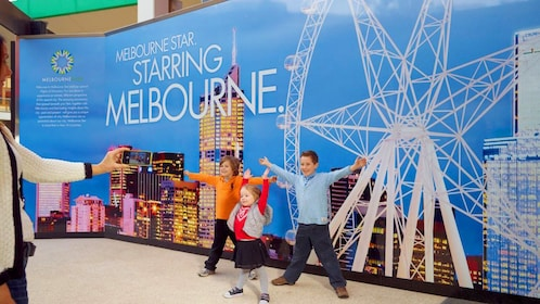 Kids posing next to a sign of the Melbourne Star
