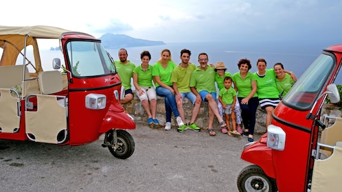 A tourist group posing at a scenic view with scooters