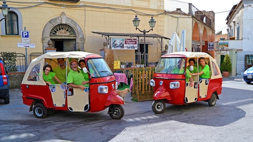 Two groups of tourists in scooter cabs