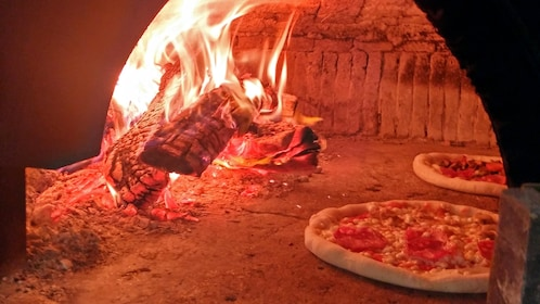 Two pizzas in a wood fired pizza oven