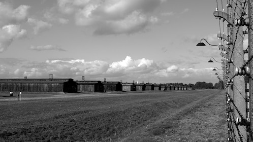 Barbed wire fence and rows of barracks inside Auschwitz-Birkenau in Poland