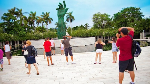 group taking photos of a hand sculpture in Miami