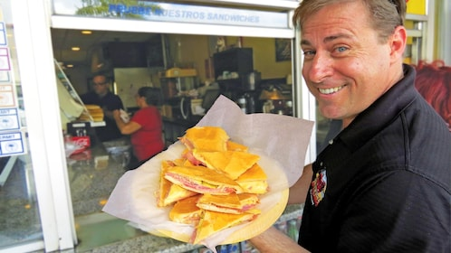 man holding up a platter of sandwiches in Miami
