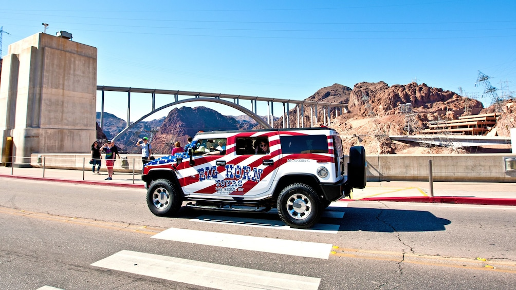 Show item 1 of 5. Tour Jeep parked on road at Hoover Dam.