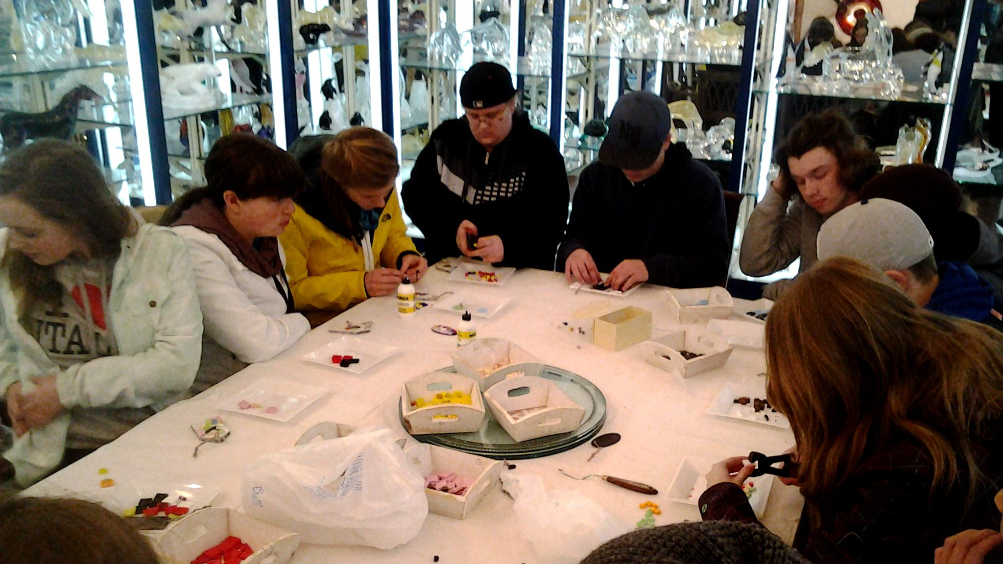 Group of tourists sit around a table and assemble crafts for glass blowing