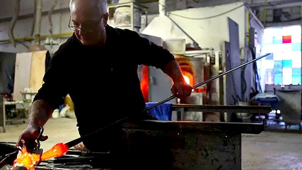 Glass blower sculpts molten glass in his shop