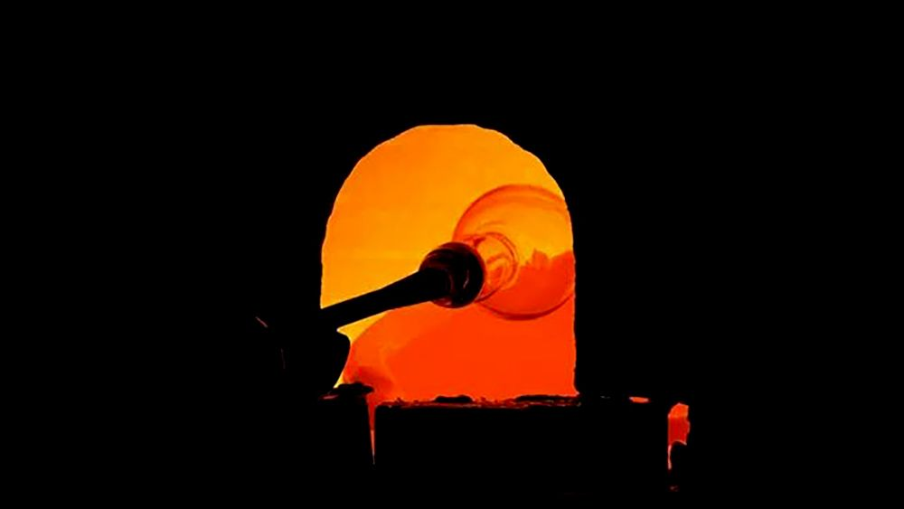 Molten glass on a pole is heated up in a kiln