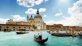 Show item 5 of 5. Man stands up in Gondola in the canals of Venice