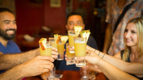 Group toasting with cocktails at a bar in Puerto Vallarta