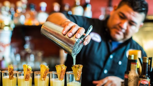 Bartender pouring cocktails at a bar in Puerto Vallarta