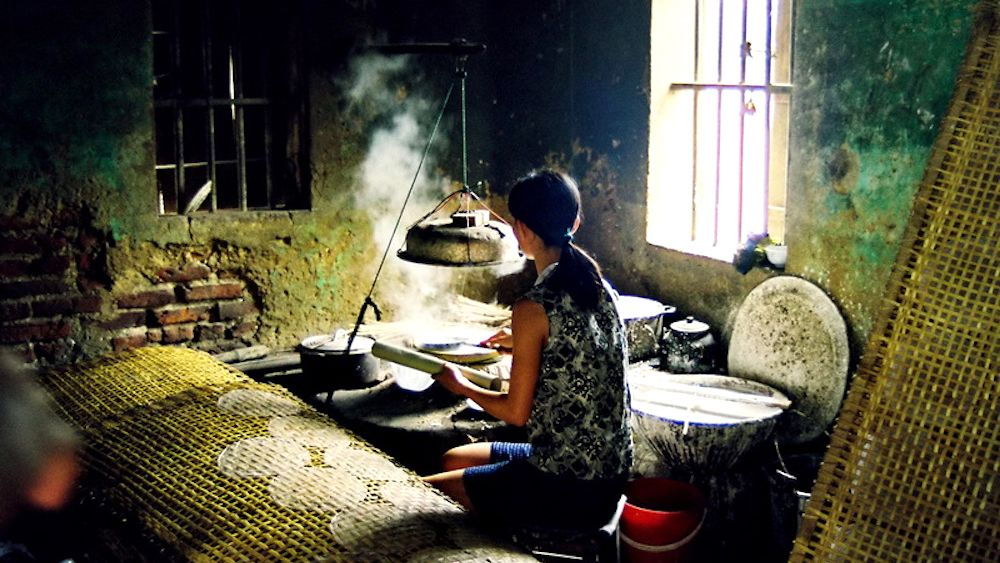 Woman cooks a meal in Tho Ha Village