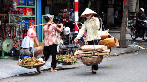 Locals carrying goods down Hanoi street
