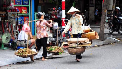 Locals carrying goods down Hanoi street
