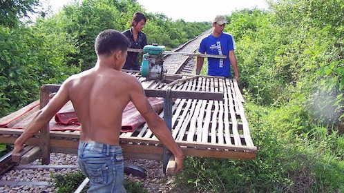 men carrying a small rail cart away from the tracks in Cambodia