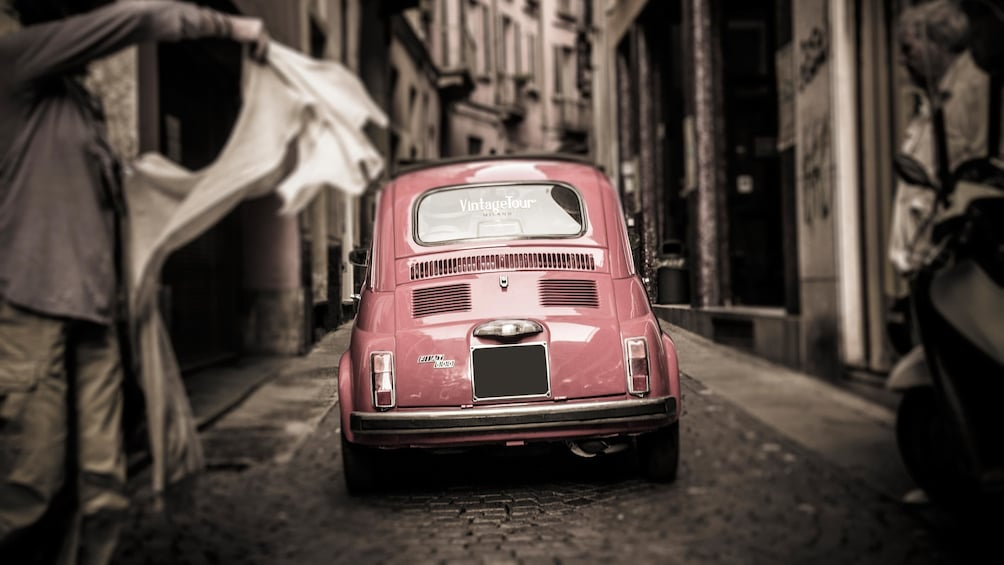 Show item 5 of 5. driving a Fiat car through a narrow street in Italy