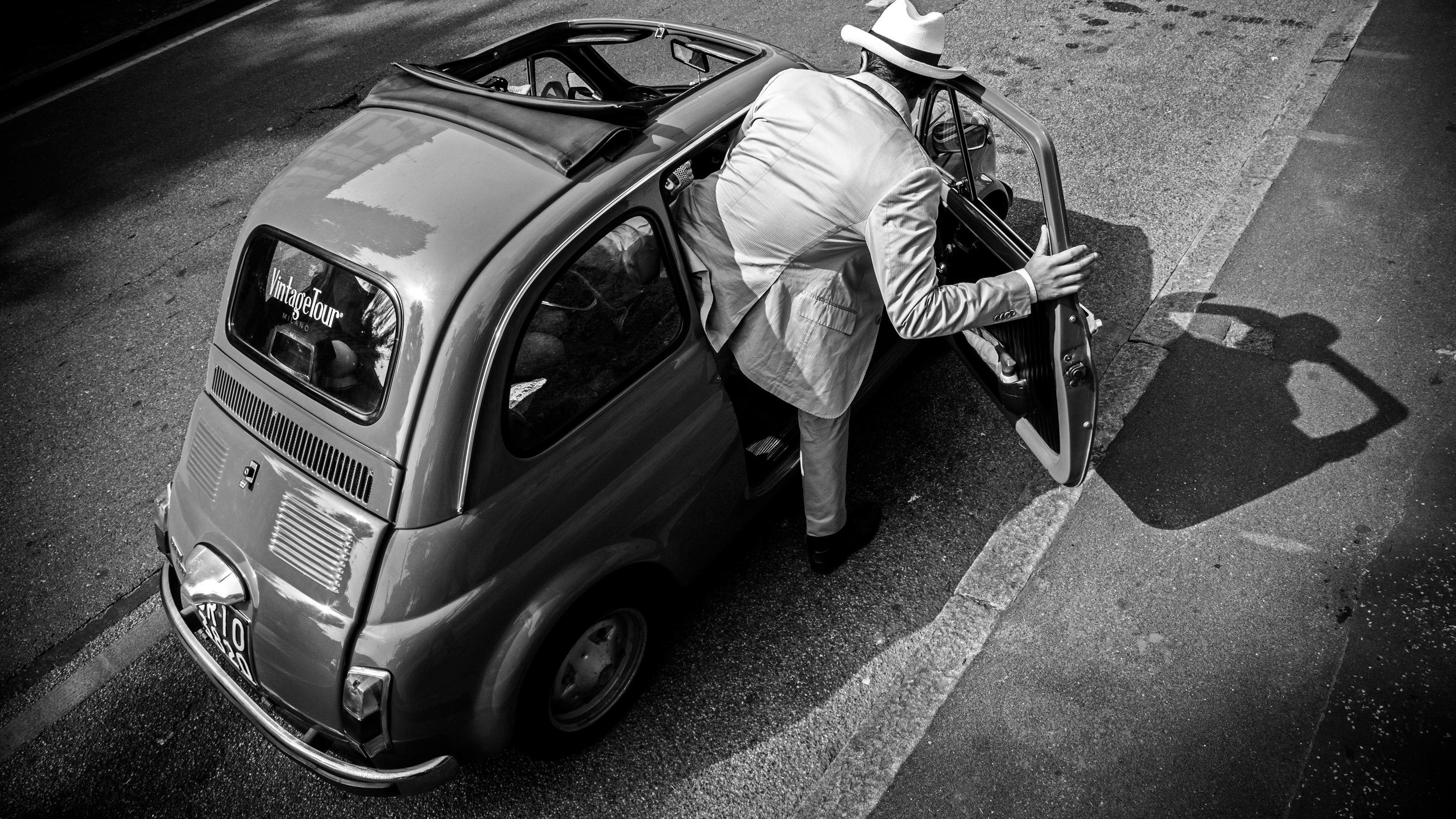 man getting in vintage Fiat vehicle in Italy