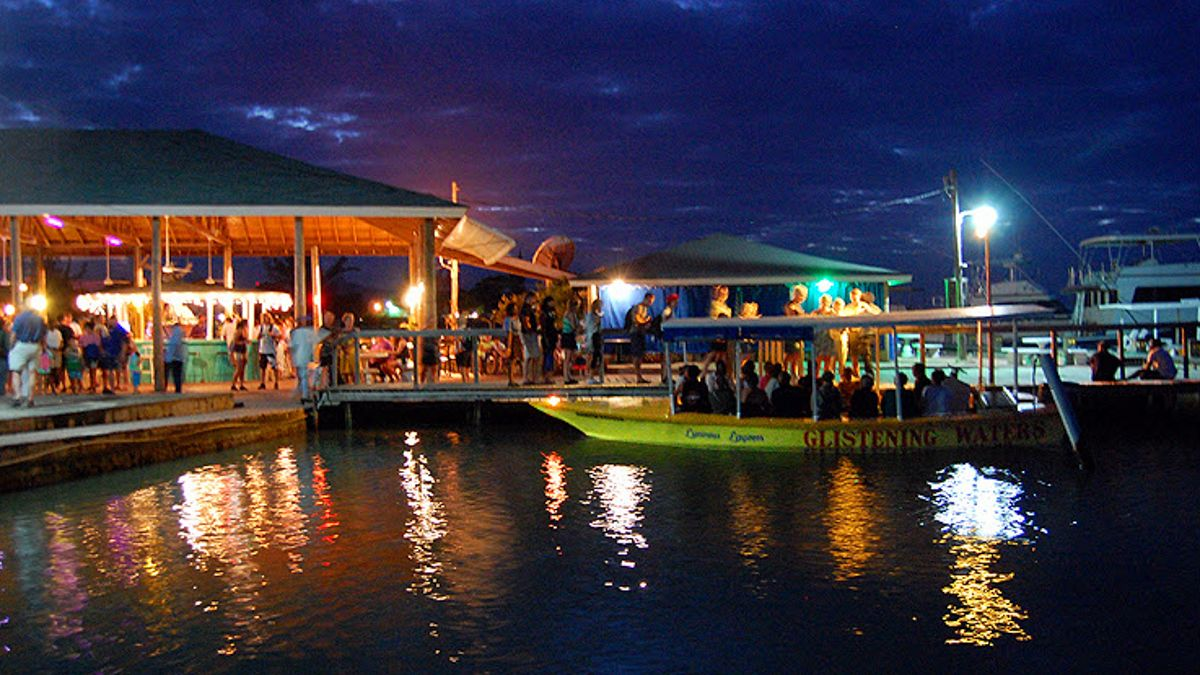 Boarding dock for tour boats at night filled with several people.