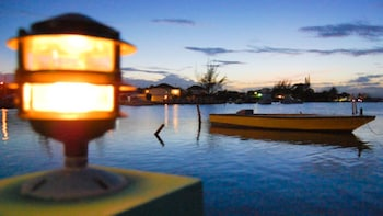 Show item 3 of 8. Evening view of lagoon with empty boat in the distance.