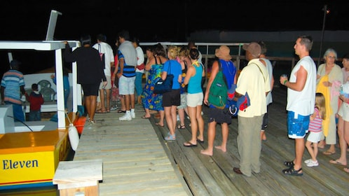 Angled view of people boarding tour boats at night.