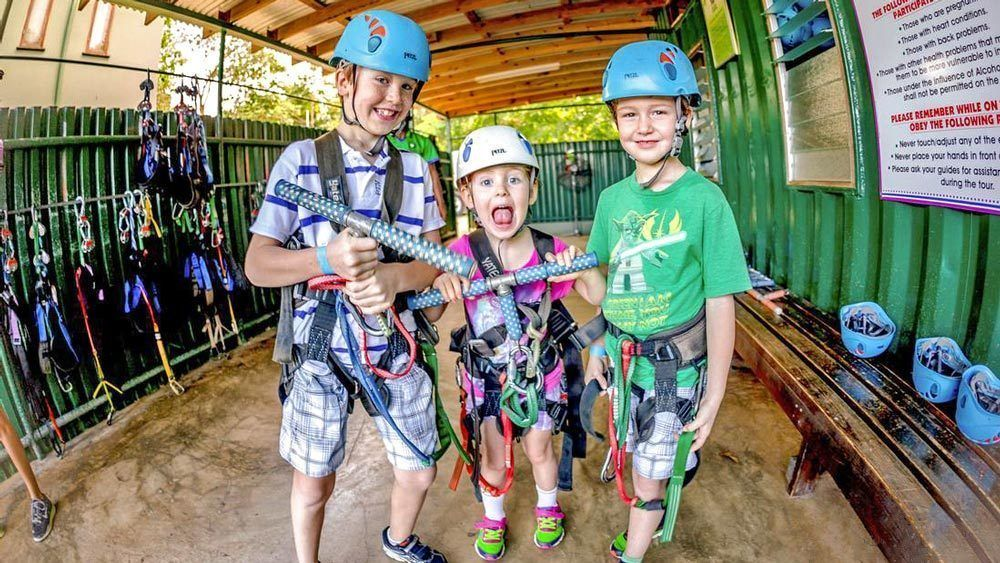 Three children harnessed up to go zipling