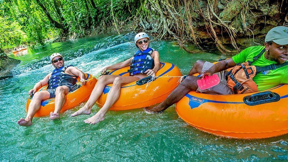 Three people on inner tubes floating down a river