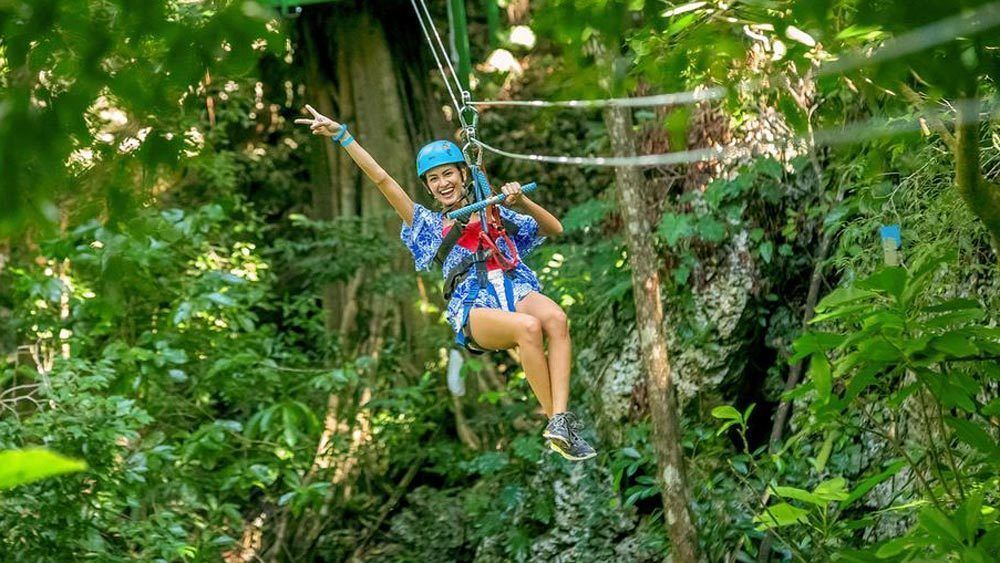 A woman poses for the camera gliding on a zipline