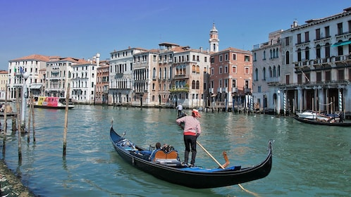 man rowing gondola on canal in venice