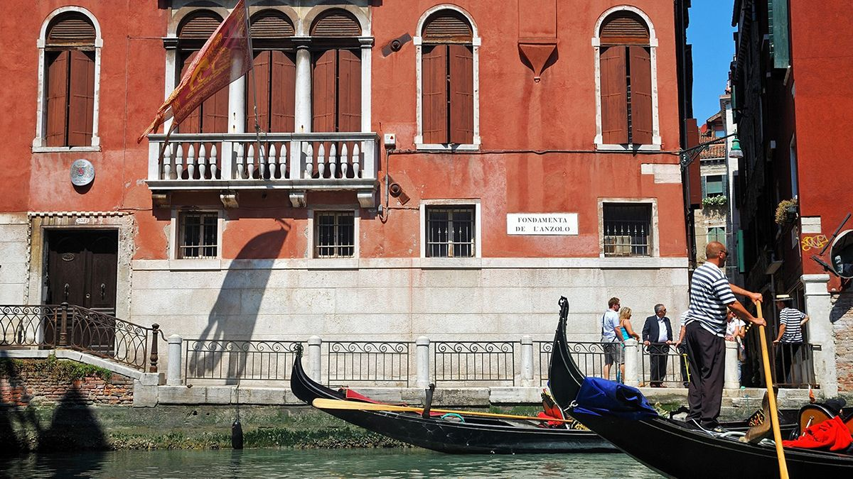 red building from gonola on canal in Venice
