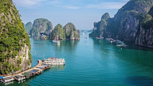 boats docked around a river mountain in Vietnam