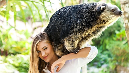 Woman posing with animal on neck.